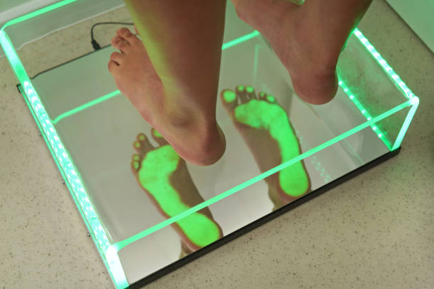 Foot step analysis on feet scanner - footprints visible in green light on plastic panel stock photo