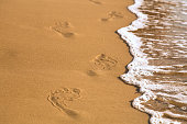 Foot steps printed on the sand beach, white sea foam and waves. Vacation or travel concept.