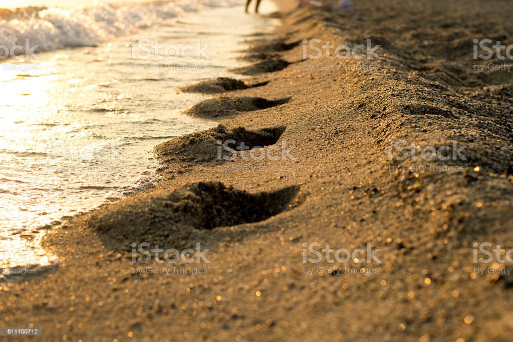 Foot steps shape in sand on beach stock photo