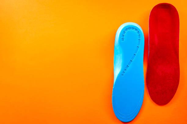 Soporte de pie y concepto de pies sanos con plantillas de zapatos ortopédicos aisladas en fondo anaranjado con Copyspace - foto de stock