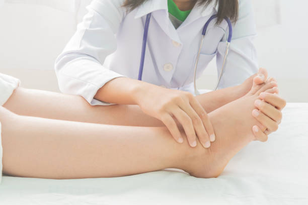 Foot swelling in pregnant women and doctor on bed stock photo