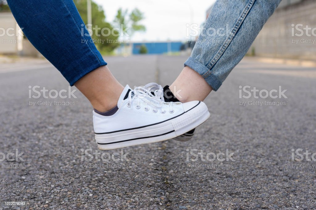 Foot tap. New novel greeting to avoid the spread of coronavirus. Two women friends meet in a British street. Instead of greeting with a hug or handshake, they touch their feet together instead. social distance Adult Stock Photo