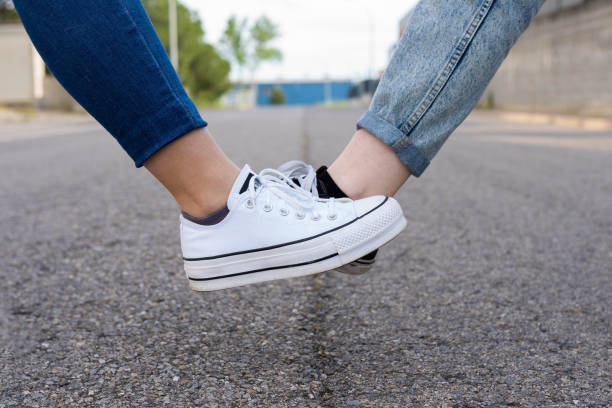Foot tap. New novel greeting to avoid the spread of coronavirus. Two women friends meet in a British street. Instead of greeting with a hug or handshake, they touch their feet together instead. social distance avoidance stock pictures, royalty-free photos & images