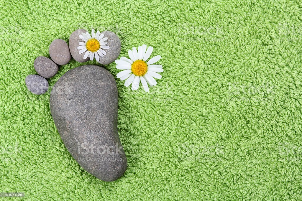 Foot with chamomile on green towel stock photo