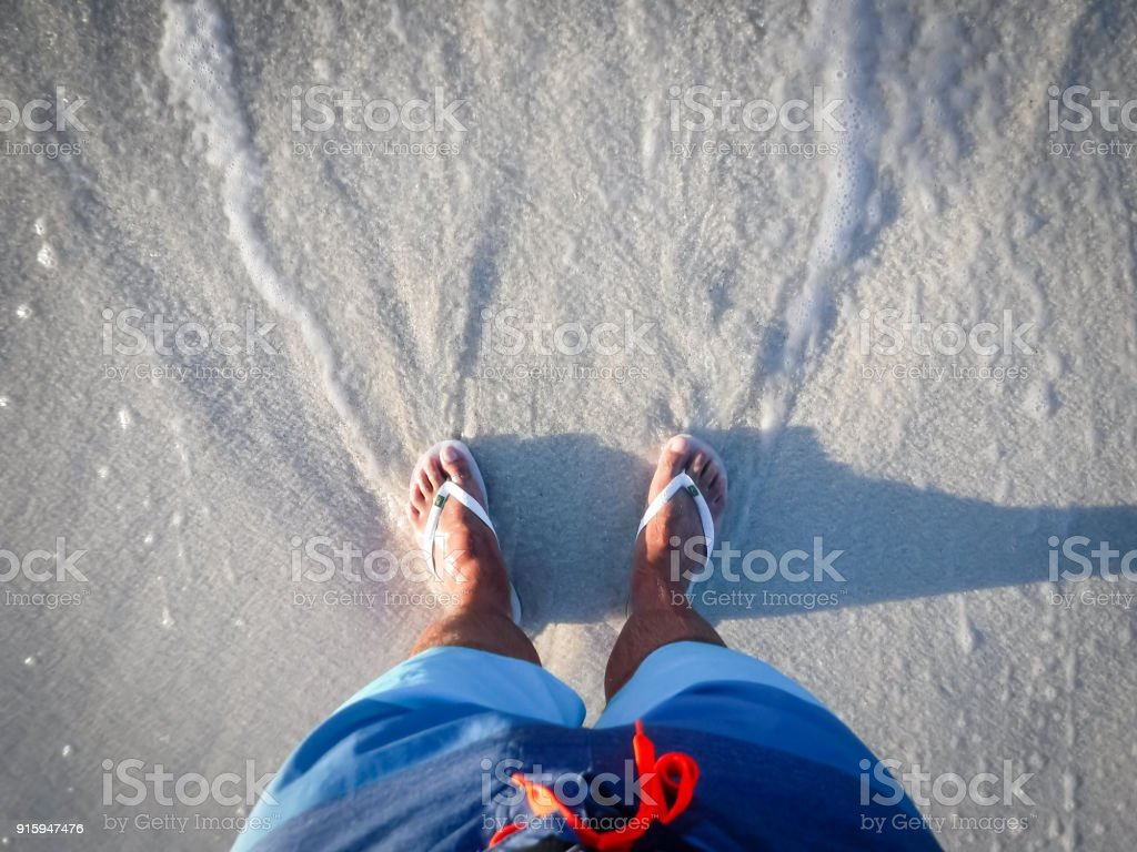 foot with slippers getting wet in the beach stock photo
