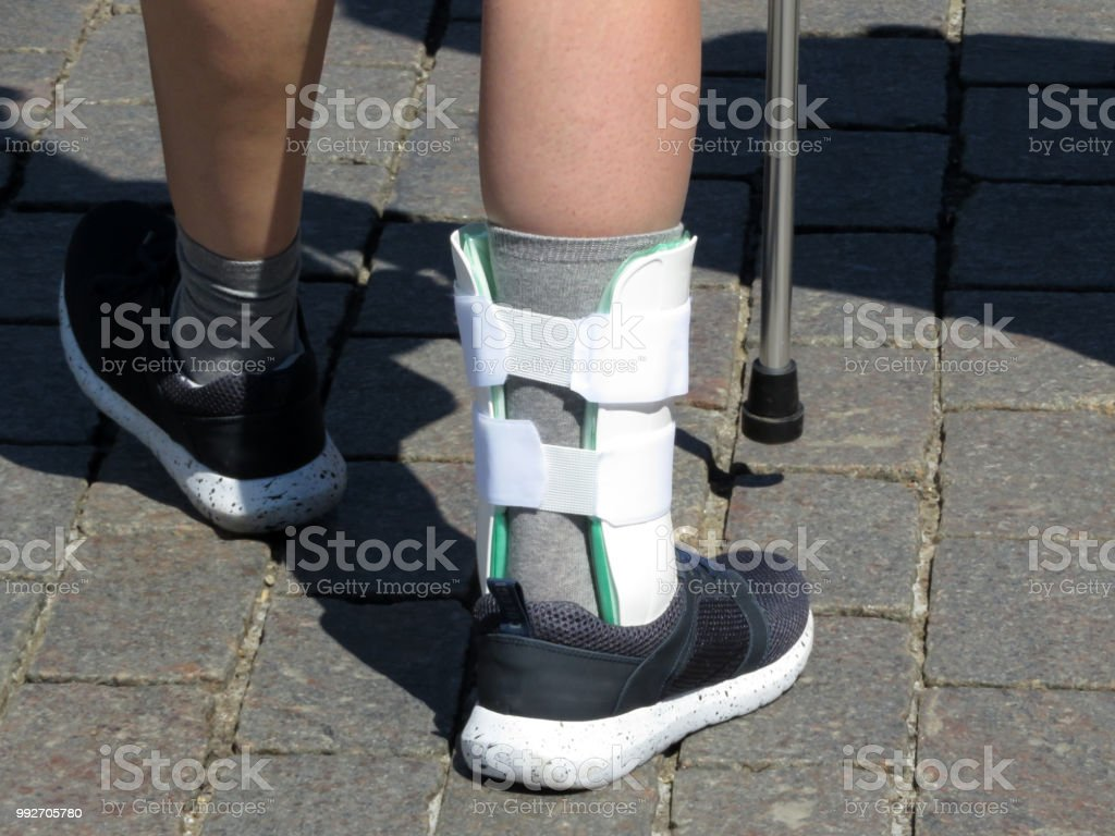 Foot with the splint, orthosis for leg. Person with cane walking after a broken or sprain legs stock photo
