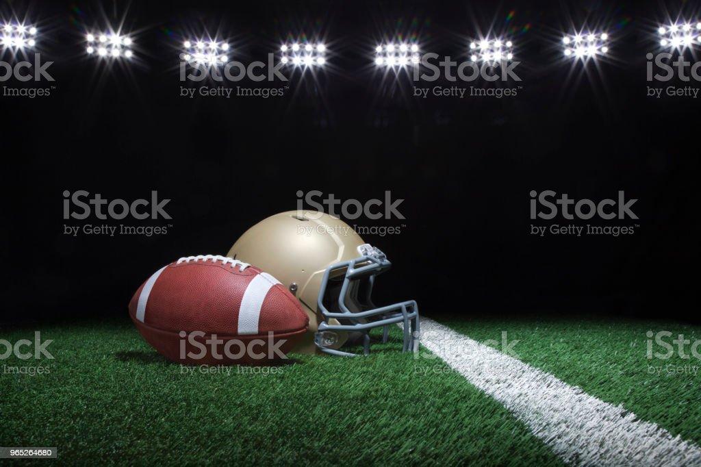 Football and helmet on field at night with lights zbiór zdjęć royalty-free