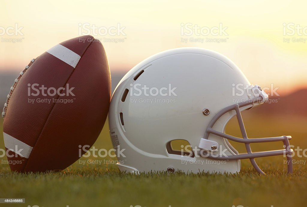 Football and Helmet on the Field at Sunset stock photo