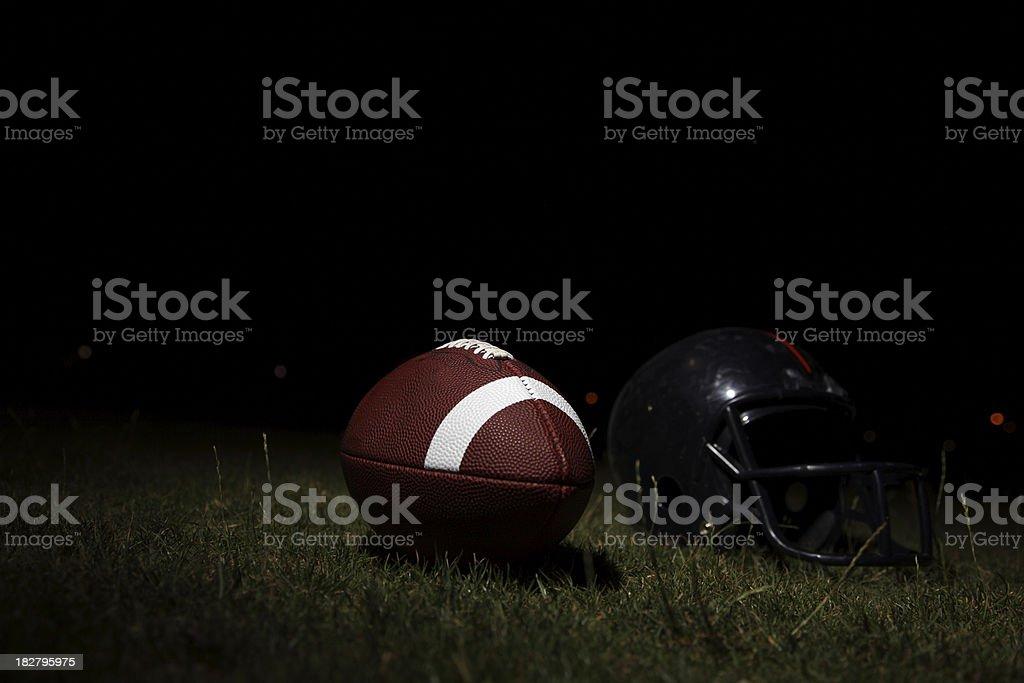 studio shot of football helmet and football