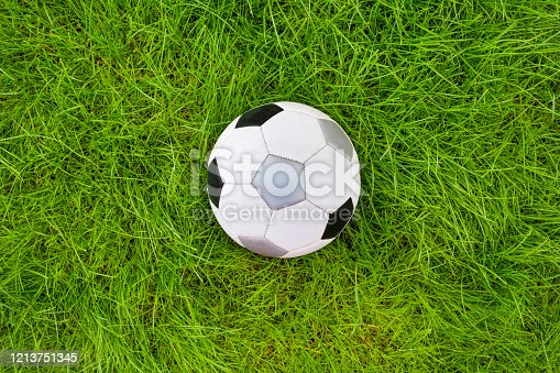 931661614 istock photo A football ball on green grass. A view from above. 1213751345