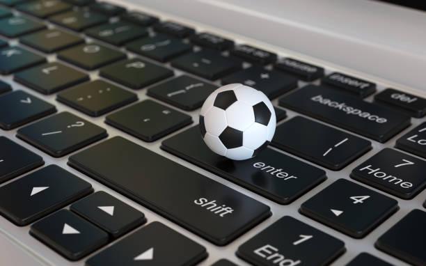 Football ball, soccer ball, on laptop keyboard stock photo