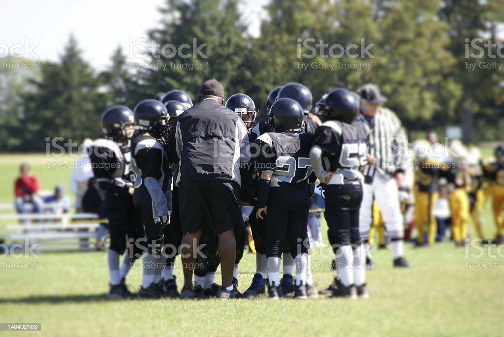 Football Coach in Huddle with Team stock photo