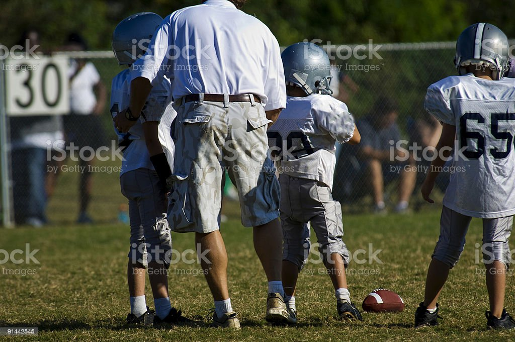 Football Coach instructing Football Players during a Football Game royalty-free stock photo