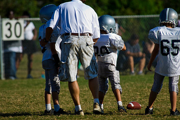 Football Coach instructing Football Players during a Football Game  line of scrimmage stock pictures, royalty-free photos & images
