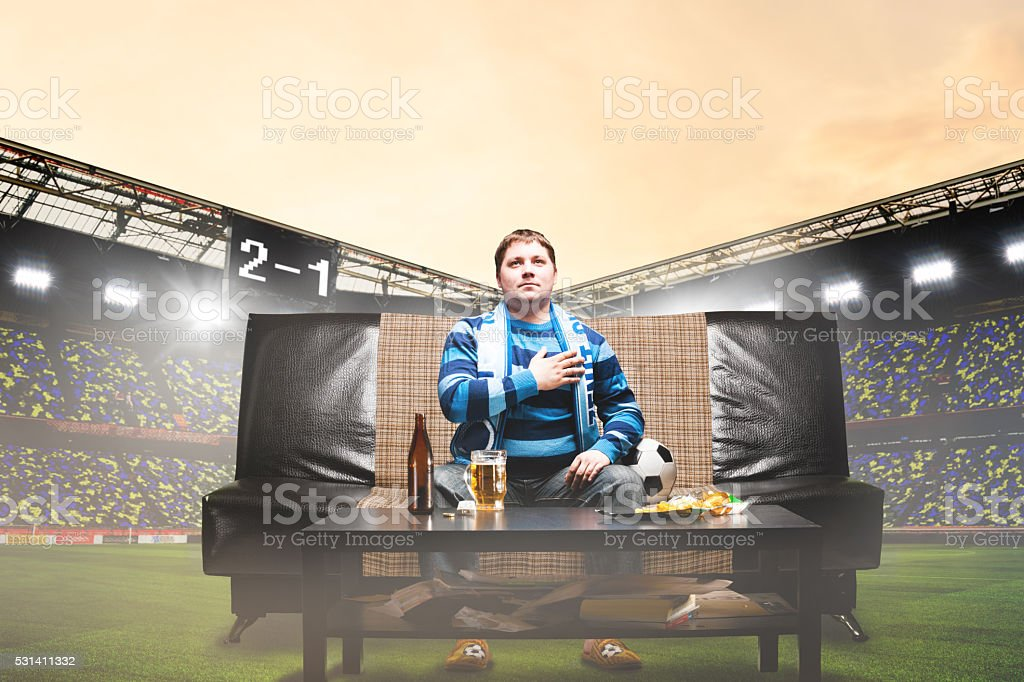 football fan on sofa at stadium stock photo