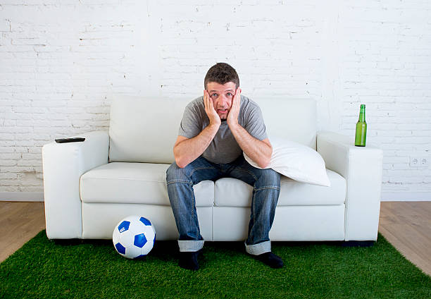 football fan watching tv match on sofa with grass carpet – Foto