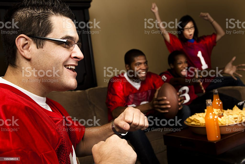 Football fans at home watching the game on television. Cheering. royalty-free stock photo