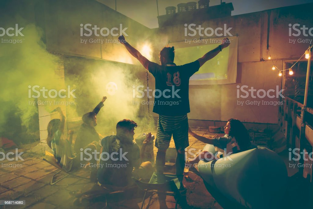 Football fans cheering while watching the game stock photo