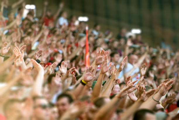 football fans clapping on the podium of the stadium - crowded stock pictures, royalty-free photos & images