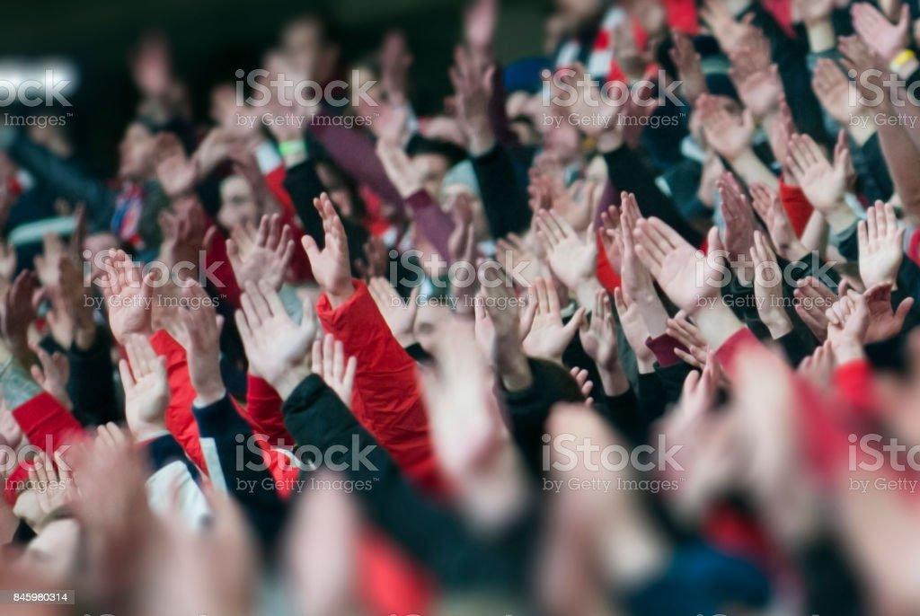 Aficionados al fútbol aplaudiendo en el podio del estadio - foto de stock