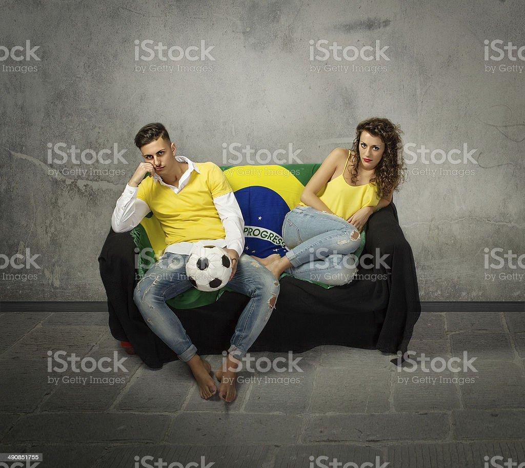 Os fãs do futebol depressão em um sofá - foto de acervo
