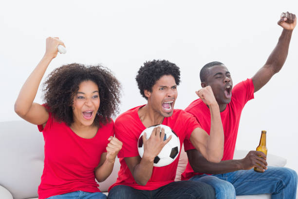 Football fans in red sitting on couch cheering stock photo