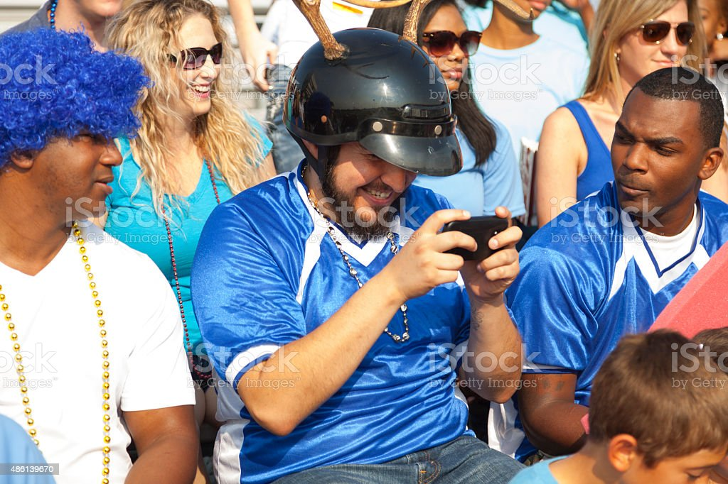 Football fans watching football game. Fan with cell phone. Stadium. stock photo