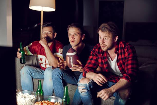voetbal fans kijken match met bieren en snacks - football friends tv night stockfoto's en -beelden