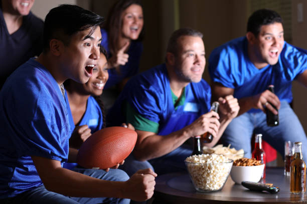 Football fans watching the game at home on television. stock photo