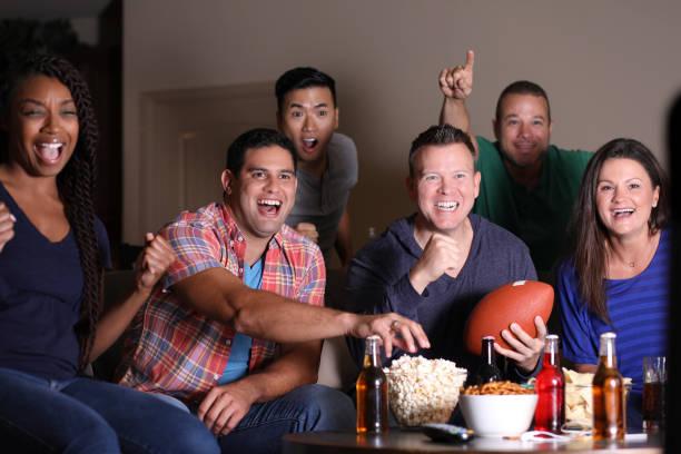Fußball-Fans das Spiel zu Hause im Fernsehen beobachten. – Foto