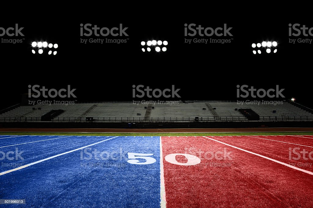 Groomed football field at night. White letters are stenciled onto the...