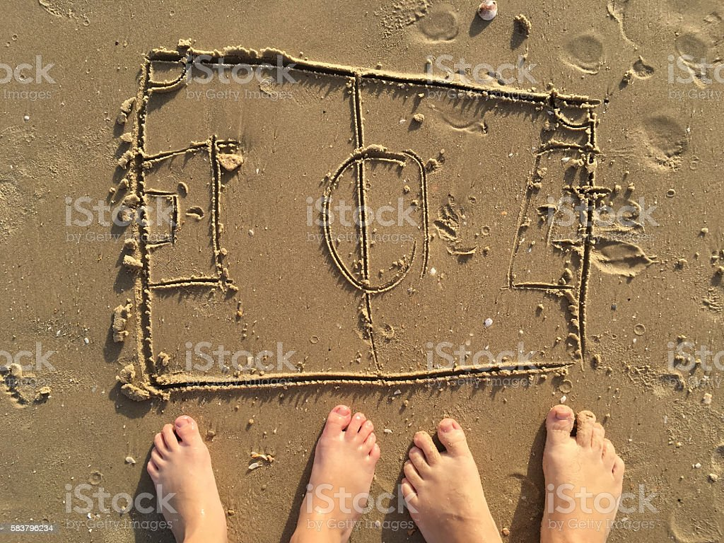 Football field drawing on sand beach. stock photo