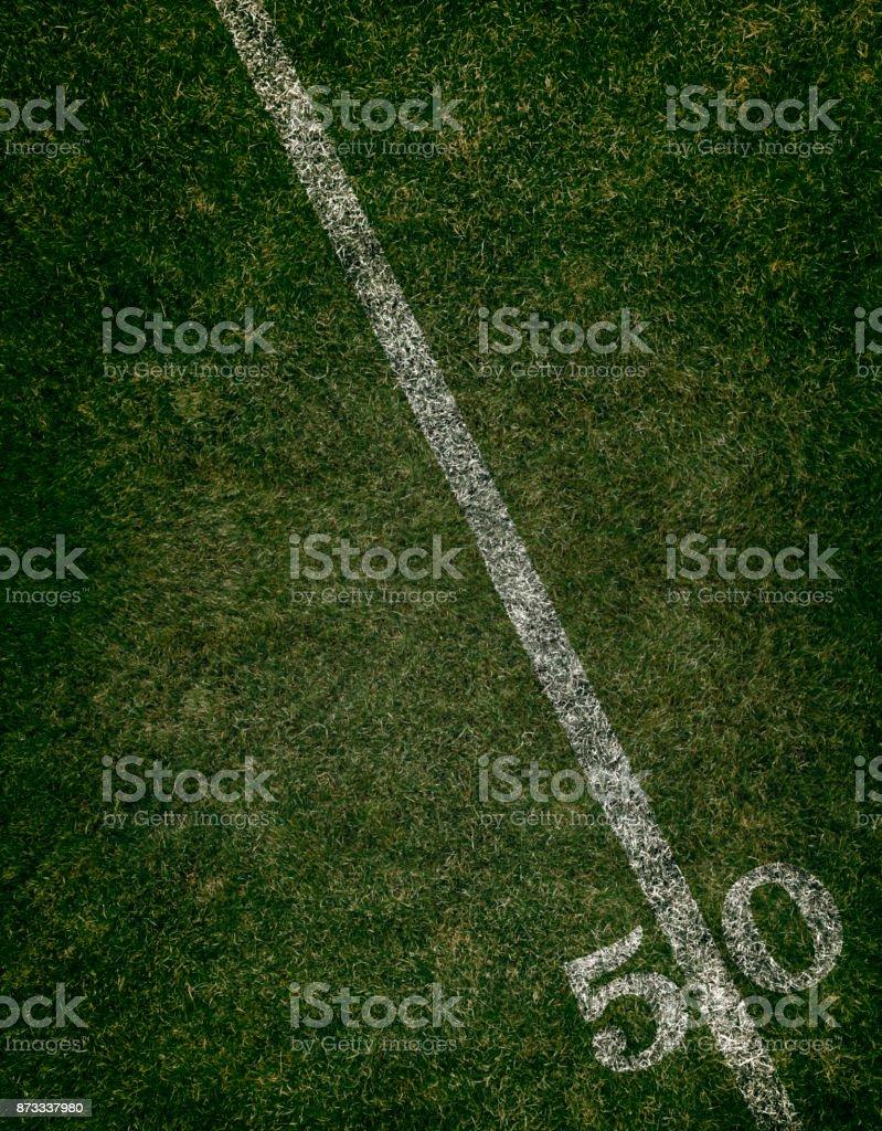 Football field ground fifty yard line. Friday night lights.