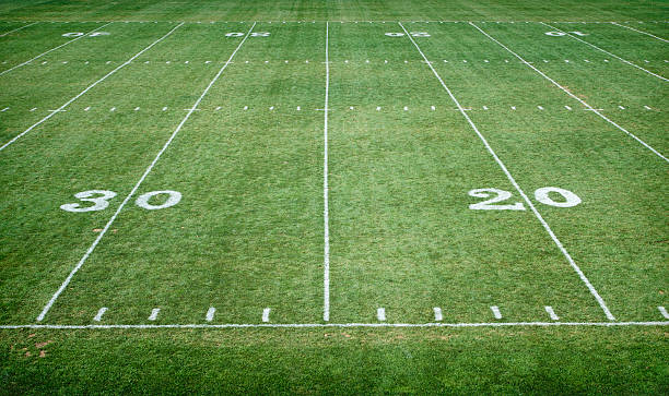 Football Field Horizontal A wide view of a football field with white painted yard lines line of scrimmage stock pictures, royalty-free photos & images