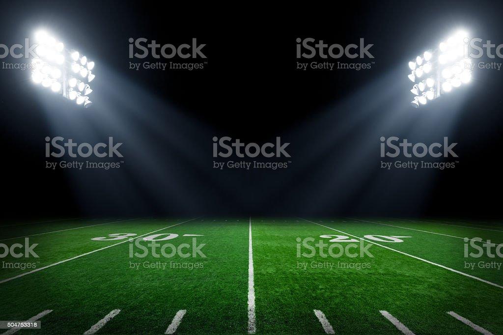 Football field at night with stadium lights.
