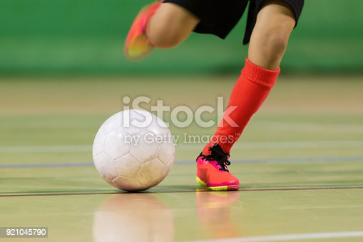 istock Football futsal training for children. Indoor soccer young player with a soccer ball in a sports hall. Sport background. 921045790