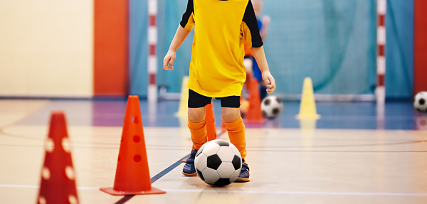 istock Football futsal training for children. Soccer training dribbling cone drill. Indoor soccer young player with a soccer ball in a sports hall. Player in orange uniform. Sport background 1049420470