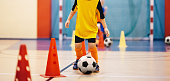Football futsal training for children. Soccer training dribbling cone drill. Indoor soccer young player with a soccer ball in a sports hall. Player in orange uniform. Sport background