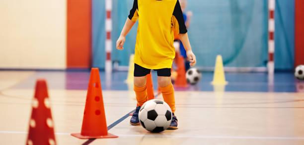 treinamento de futsal de futebol para crianças. broca cone drible de treinamento de futebol. jovem jogador de futebol com uma bola de futebol em um salão de esportes. jogador em uniforme laranja. fundo do esporte - comodidades para lazer - fotografias e filmes do acervo
