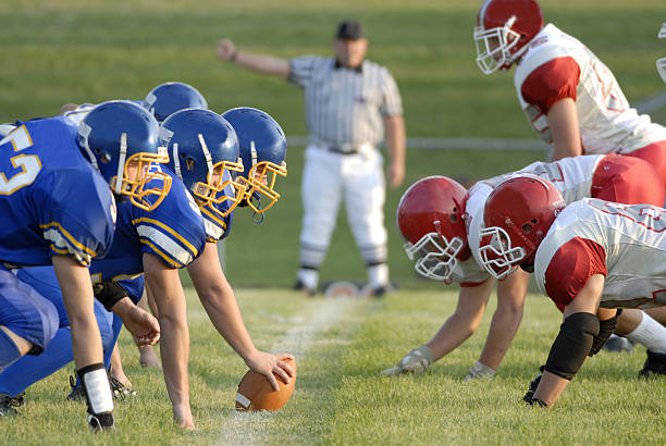 Football Game line of scrimage American high school football focusing on the line of scrimmage. line of scrimmage stock pictures, royalty-free photos & images