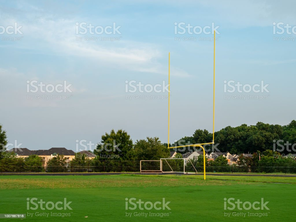 Football goal post at a high school field in the evening sun stock photo