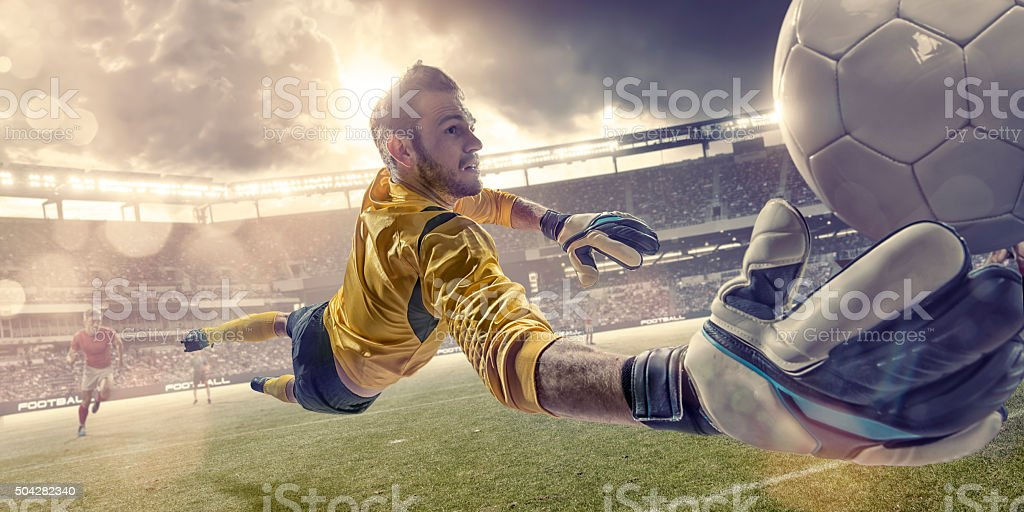 Football Goalkeeper Diving To Save Ball During Soccer Match stock photo