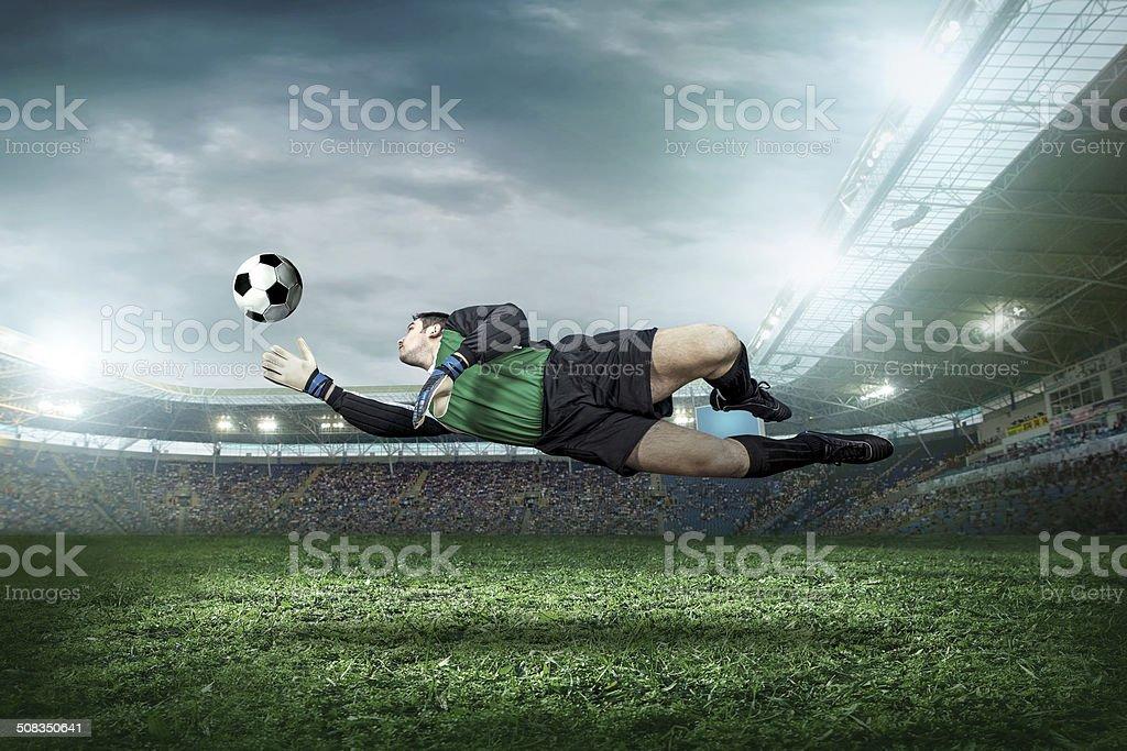 Football goalkeeper in action on field of stadium stock photo