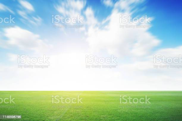Photo of Football green field with cloud blue sky background. Landscape outdoor sport