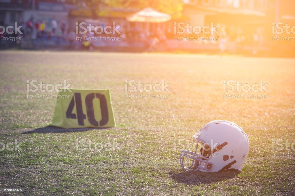 Football helmet lying on green grass field stock photo