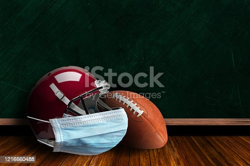 Football helmet wearing surgical mask on a background chalk board with copy space for text. Concept of COVID-19 coronavirus pandemic affecting American football season due to game or league suspensions or cancellations.
