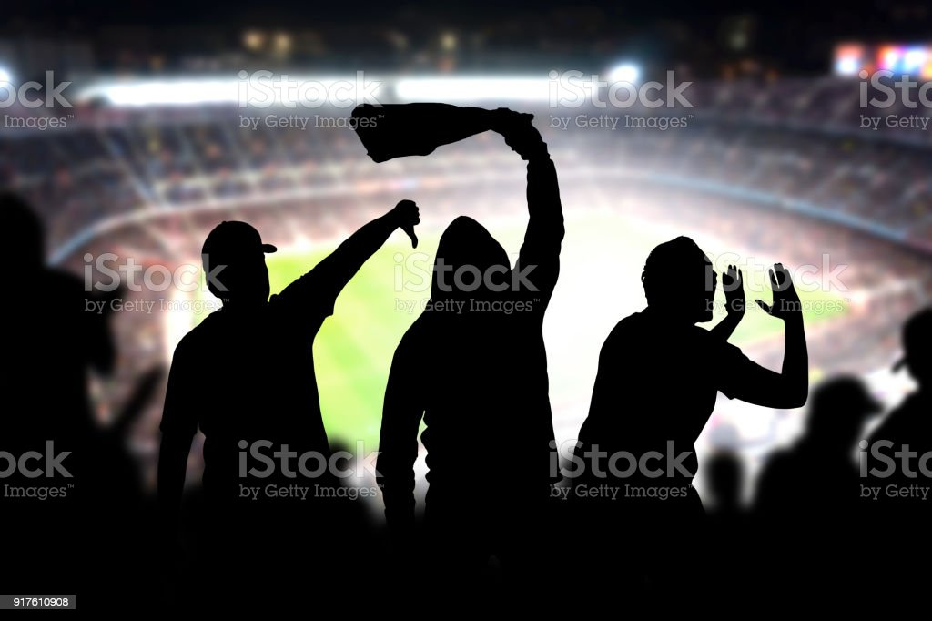 Football hooligans in game. Angry soccer fans shouting and booing in the crowd. Losing team fans got mad. stock photo