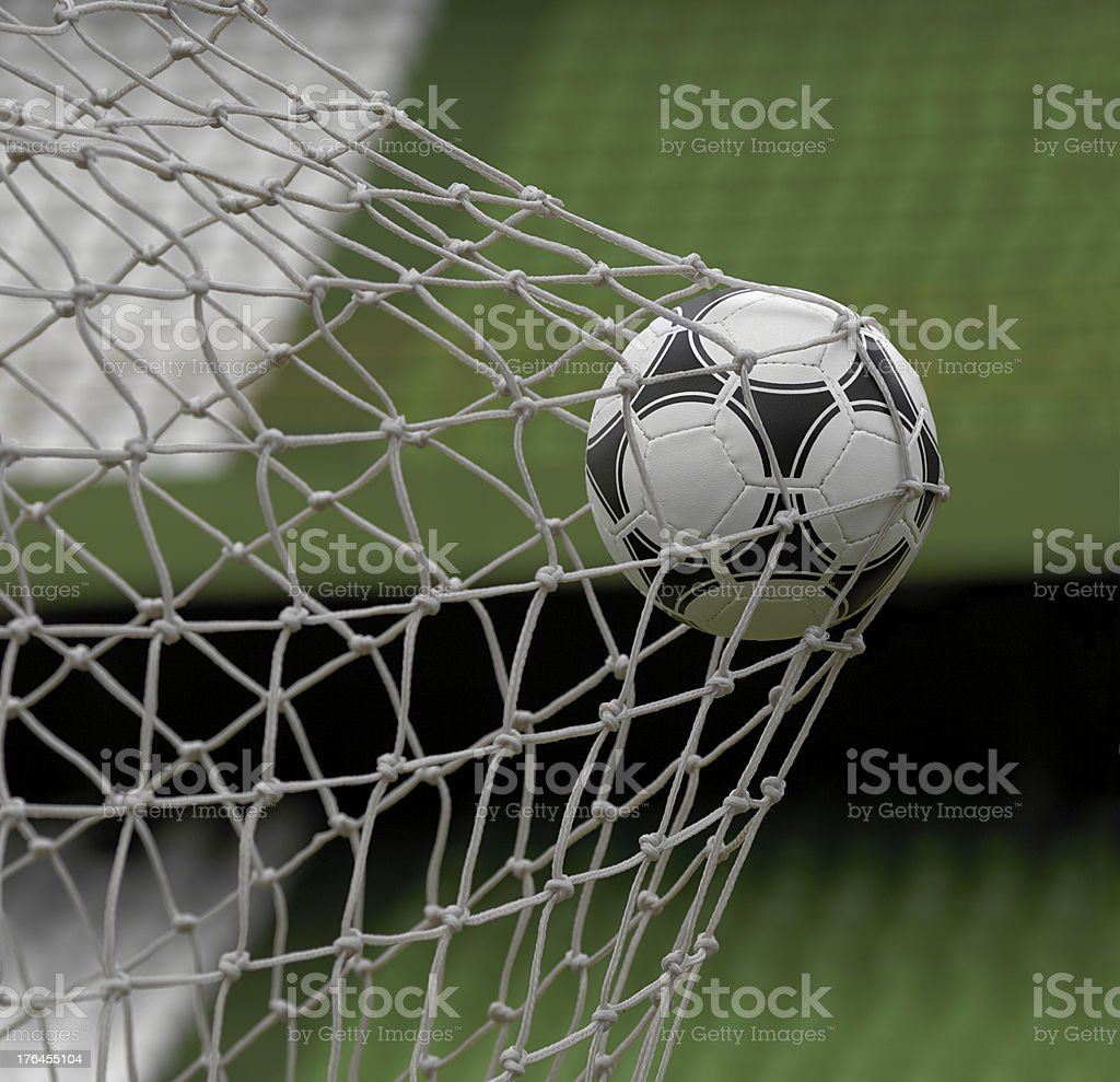 Football in back of goal net against stadium background royalty-free stock photo