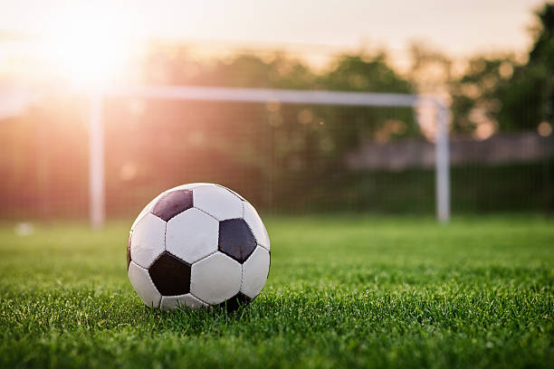 football in the sunset - soccer goal stockfoto's en -beelden