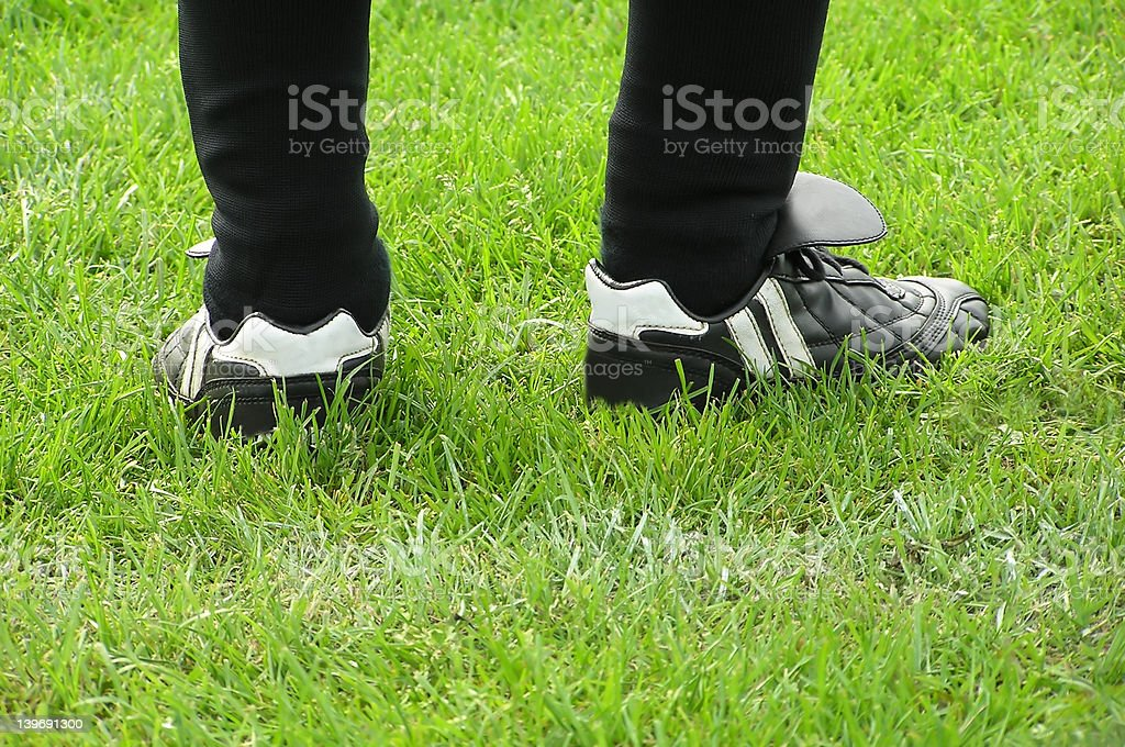 Football legs on green grass stock photo